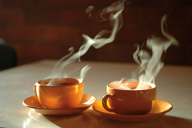 Two orange cups of steaming tea